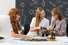 Studenten die hun nieuw project verklaren aan een leraar stock afbeelding
