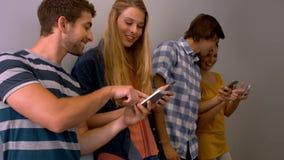 Studenten die hun smartphone in de zaal van de universiteit gebruiken stock video