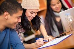 Studenten, die ihre Aufgabe schreiben lizenzfreie stockbilder