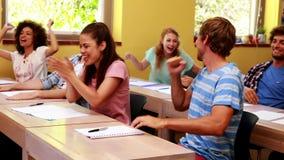 Studenten die in klaslokaal en het toejuichen zitten stock video