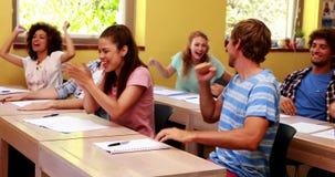 Studenten die in klaslokaal en het toejuichen zitten stock footage
