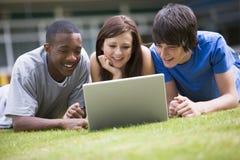 Studenten die laptop op campusgazon met behulp van Royalty-vrije Stock Foto's