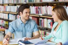 Studenten die met boeken aan examen in bibliotheek voorbereidingen treffen Stock Afbeelding