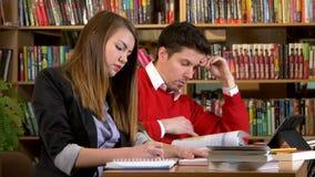 Studenten die met boeken aan examen in bibliotheek voorbereidingen treffen stock video
