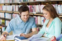 Studenten die met boeken aan examen in bibliotheek voorbereidingen treffen Stock Foto