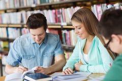 Studenten die met boeken aan examen in bibliotheek voorbereidingen treffen Stock Fotografie