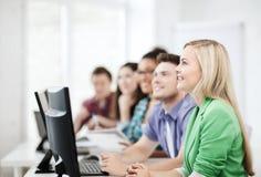Studenten die met computers op school bestuderen Stock Foto's