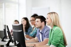 Studenten die met computers op school bestuderen Stock Afbeelding