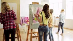 Studenten die met schildersezels op kunstacademie schilderen stock footage