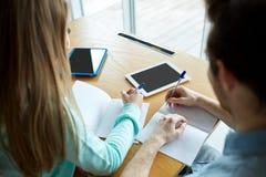 Studenten die met tabletpc aan notitieboekjes schrijven Stock Foto