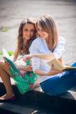Studenten, die mit einem Buch auf Straße sitzen Lizenzfreie Stockfotografie