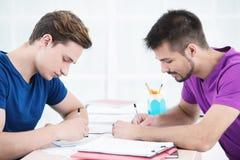 Studenten die nota's in klaslokaal nemen Stock Afbeeldingen