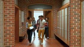 Studenten die onderaan gang aan kast lopen stock videobeelden