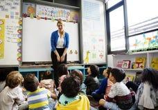 Studenten die op de vloer zitten die aan leraar luisteren stock afbeeldingen