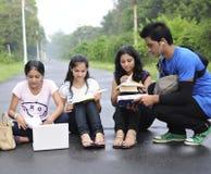 Studenten die op de weg zitten en nota's delen. Stock Foto