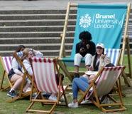 Studenten die op ligstoelen in Brunel Universitair Londen ontspannen royalty-vrije stock fotografie