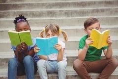 Studenten die op stappen zitten en boeken lezen stock foto