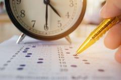 Studenten die optische vorm van gestandaardiseerde examens nemen dichtbij Alarmcl Royalty-vrije Stock Afbeelding