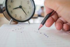 Studenten die optische vorm van gestandaardiseerde examens nemen dichtbij Alarmcl Royalty-vrije Stock Foto