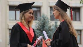 Studenten die over toekomst na graduatieceremonie spreken in park, onderwijs stock footage