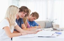 Studenten die samen bij de lijst bestuderen Stock Fotografie