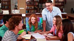 Studenten die samen in de bibliotheek met hun privé-leraar bestuderen stock videobeelden