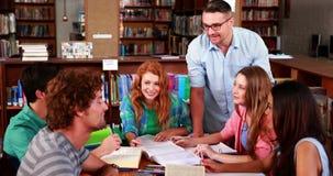 Studenten die samen in de bibliotheek met hun privé-leraar bestuderen stock footage