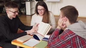 Studenten die samen en een boek bestuderen lezen stock videobeelden