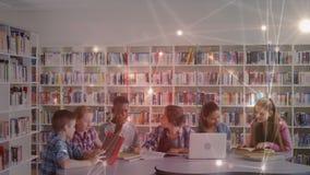 Studenten die samen over boeken en laptop op elkaar inwerken stock video