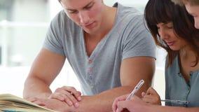 Studenten die samen terwijl het bestuderen zitten stock videobeelden