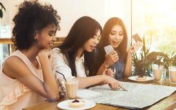 Studenten, die sich entscheiden, Karten mit Smartphone und Kreditkarte zu kaufen lizenzfreies stockbild