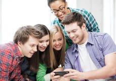 Studenten die smartphone op school bekijken Stock Foto