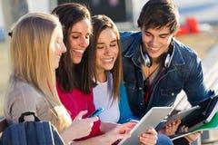 Studenten, die Spaß mit Smartphones und Tabletten nach Klasse haben Lizenzfreie Stockbilder