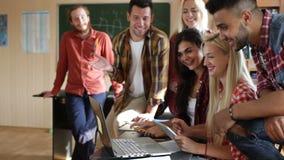 Studenten die tabletcomputer en laptop de glimlach van de mensengroep gebruiken stock video
