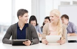 Studenten, die Tabletten-PC im Vortrag an der Schule betrachten Stockbild