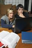 Studenten die thuiswerk met laptop doen Royalty-vrije Stock Afbeeldingen