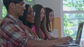 Studenten die tijdens klasse leunen, die met laptops werken stock footage