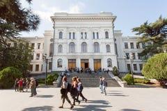 Studenten die voorbij gevestigd hoofdgebouw van de Universiteit van de Staat van Tbilisi lopen, 1918 Royalty-vrije Stock Foto's