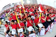 Studenten, die wie Zuschauer während sich amüsieren Wiederholung 2013 der Nationaltag-Parade-(NDP) Stockfotografie
