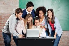 Studenten die zich met Klasgenoten bevinden terwijl Leraar stock afbeeldingen