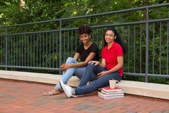 2 Studenten, die zusammen auf dem Campus sitzen stockfotos