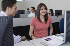 Studenten, die zusammen am Computertisch sitzen Stockfotos