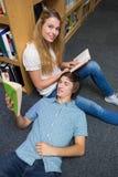 Studenten, die zusammen in der Bibliothek lesen Lizenzfreie Stockfotografie
