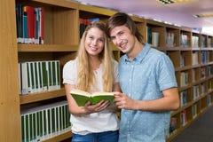 Studenten, die zusammen in der Bibliothek lesen Stockfotos