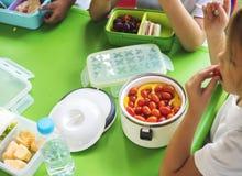 Studenten, die zusammen Lebensmittel-Mittagspause essen lizenzfreie stockfotografie