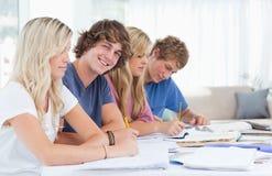 Studenten, die zusammen mit einem Mann betrachtet die Kamera studieren   Lizenzfreie Stockfotos