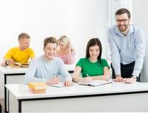 Studenten en de leraar die in een klaslokaal leren Stock Foto's