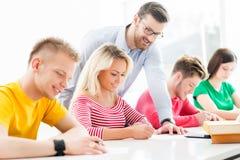 Studenten en de leraar in een klaslokaal Stock Afbeeldingen