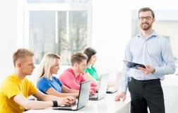 Studenten en de leraar in een klaslokaal Stock Foto's