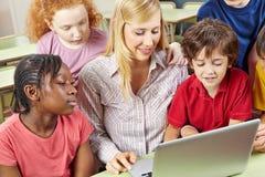 Studenten en leraar die met laptop computer werken Stock Afbeelding